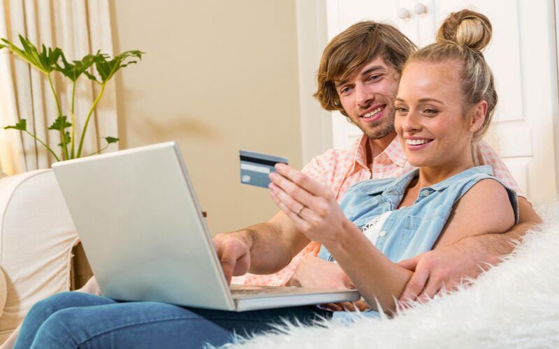 mand og damne med dankort kigger på computer